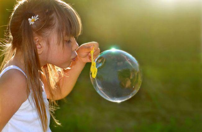 девочка дует пузыри