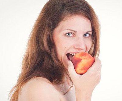 женщина ест персик